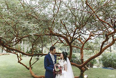 Casamento ao ar livre - RJ | Noiva segurando um buque de flores, olhando apaixonada para o noivo, entre as árvores do Lago Buriti, no Rio de Janeiro.