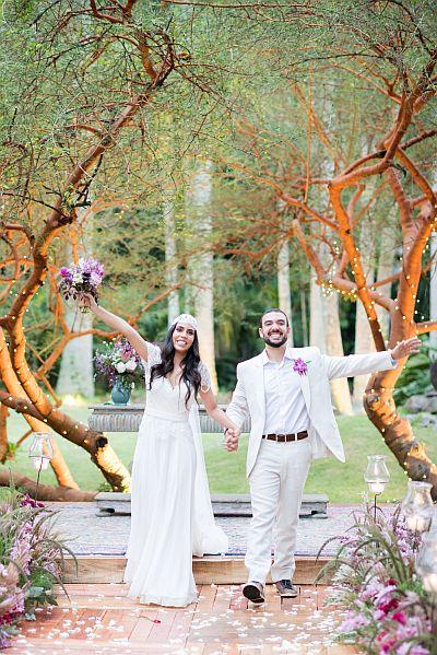 Casamento ao ar livre Rio de Janeiro - Noiva segurando um buque de flores de braço levantado, segurando a mão do noivo sorridentes e radiantes, entre árvores do Lago Buriti.