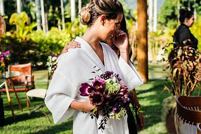 Casamento ao ar livre no RJ | Noiva segurando um buque de noiva, no momento que recebe o buque da Renata Paraiso, sorrindo emocionada, segurando o choro.
